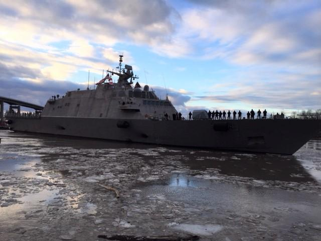 The LCS 9 crew stands on deck to bid farewell to onlookers.